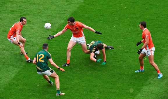 Armagh's Aaron Findon (centre) passes the ball to team-mate Tony Kernan ( left) with support from Stefan Campbell (right) in action against Shane O'Rourke and Andrew Tormey of Meath