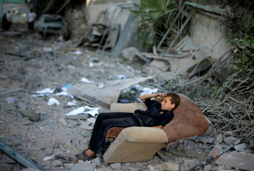 A Palestinian boy sits on a sofa outside his family's house, which witnesses said was damaged in an Israeli air strike, in Gaza City. Hamas claimed responsibility on Saturday for a deadly Gaza Strip ambush in which an Israeli army officer may have been captured, but said the incident likely preceded and therefore had not violated a U.S.- and U.N.-sponsored truce. Palestinian officials say 1,650 Gazans, most of them civilians, have been killed, including a muezzin who died in an Israeli strike on a northern mosque on Saturday.