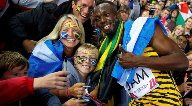 Jamaica's Usain Bolt poses for photographs with fans after Jamaica won the men's 4x100m relay final at the 2014 Commonwealth Games