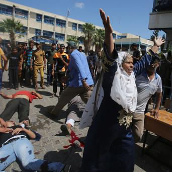 A Palestinian woman reacts as wounded and dead people lie on the ground following what witnesses said was an Israeli air strike at a United Nations-run school, where displaced Palestinians take refuge, in Rafah in the southern Gaza Strip August 3, 2014.
