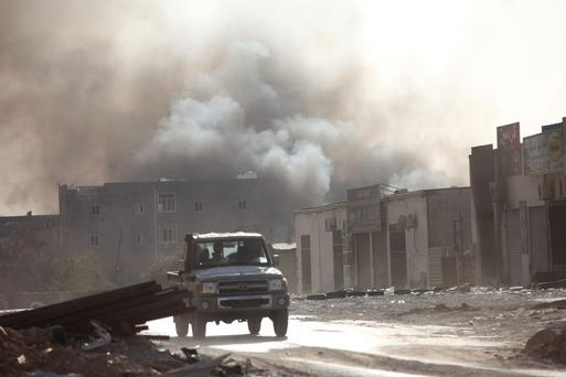 Smoke rises after rockets fired by one of Libya's militias struck and ignited a building after clashes between rival militias, in an area at Alswani road in Tripoli