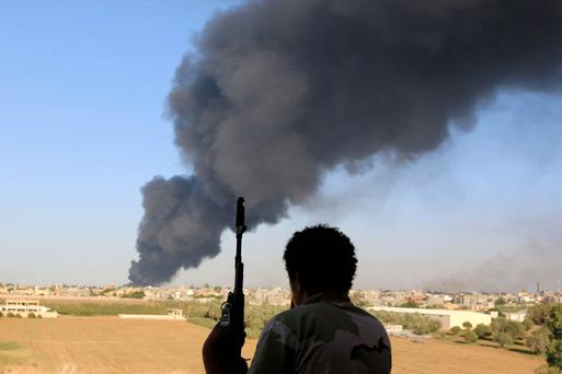 A fighter from watches as smoke rises after rockets fired by one of Libya's militias. Reuters