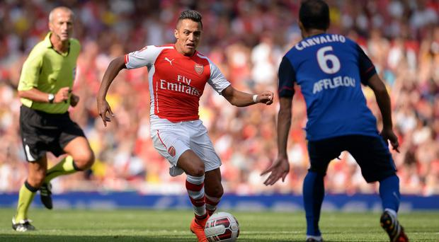 Arsenal's Alexis Sanchez runs at the Monaco defence during the Emirates Cup match