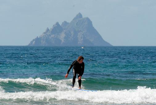 Holidaymakers enjoy some pleasant surfing at St. Finan's Bay with Skellig Michael in the background in County Kerry on Sunday. Picture: Don MacMonagle