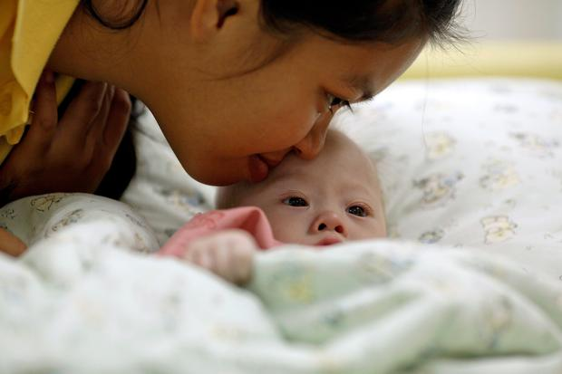 Gammy, a baby born with Down's Syndrome, is kissed by his surrogate mother Pattaramon Janbua at a hospital in Chonburi province August 3, 2014. According to Pattaramon, his Australian parents, through a local surrogate agency, asked her at her 7th month of pregnancy to terminate it because of his Down's Syndrome but she refused and kept the baby. The Australian parents instead took with them Gammy's twin sister who was born healthy. More than 3 million Thai baht ($93,360) was raised through an online campaign in Thailand in less than a day for the medical treatment of Gammy who suffers from potentially life threatening heart conditions and a serious lung infection, local media reported. REUTERS/Damir Sagolj (THAILAND - Tags: SOCIETY HEALTH)
