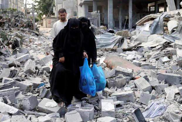Palestinian women walk upon the debris of a house which witnesses said was destroyed in an Israeli air strike, in Rafah in the southern Gaza Strip