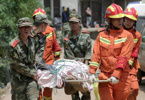 Chinese paramilitary policemen and rescuers carry a victim injured in Sunday's earthquake in the town of Longtoushan in Ludian County in southwest China's Yunnan Province Tuesday, Aug. 5, 2014. (AP Photo/Andy Wong)
