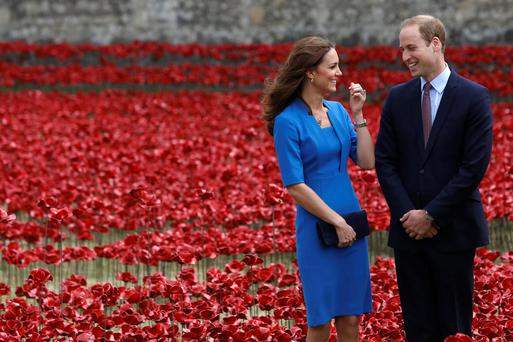 Britain's Prince William and his wife Catherine, Duchess of Cambridge stand amid the Tower of London's 'Blood Swept Lands and Seas of Red' poppy installation to commemorate the 100th anniversary of the outbreak of World War One