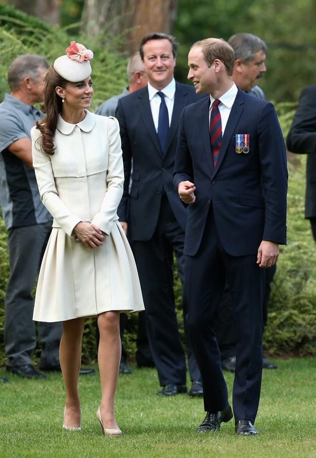 Duchess of Cambridge, the Duke of Cambridge and Prime Minster David Cameron (centre rear) walk through war graves at St Symphorien Military Cemetery as they attend a ceremony to commemorate the 100th anniversary of the outbreak of First World War