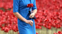The Duchess of Cambridge adds a ceramic poppy as she views the Tower of London's 'Blood Swept Lands and Seas of Red' poppy installation which commemorate the 100th anniversary of the outbreak of First World War