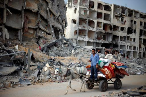 Palestinians ride a donkey cart past destroyed and badly damaged residential buildings as they return to Beit Lahiya town