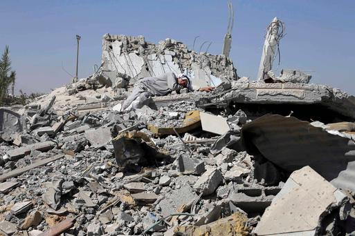 A Palestinian man lies on the ruins of his son's destroyed house in Khuzaa town, which witnesses said was heavily hit by Israeli shelling and air strikes during Israeli offensive, in the east of Khan Younis in the southern Gaza Strip. Reuters