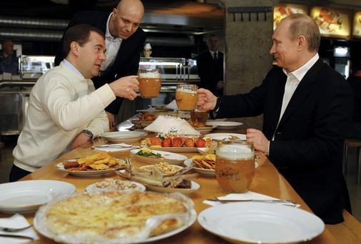Russian President Dmitry Medvedev (L) and Prime Minister and President-elect Vladimir Putin toasting with beer during a visit to a self-service restaurant in Moscow. Russia has banned food imports from the EU and USA amongst other countries.