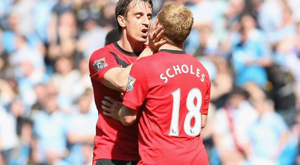 Paul Scholes is kissed by team-mate Gary Neville during Manchester United's 2010 victory over their city rivals. Scholes admits it was Neville who persuaded him to first appear as a pundit. Photo credit: John Peters/Manchester United via Getty Images