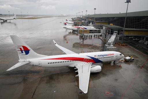 A Malaysia Airlines Boeing 737-800 plane sits on tarmac at Kuala Lumpur International Airport in Sepang, Malaysia, Friday, Aug. 8, 2014. Malaysia's state investment company said Friday it plans to make Malaysia Airlines fully government owned, removing it from the country's stock exchange before carrying out a far-reaching overhaul of the carrier that is reeling from double disasters
