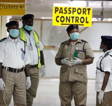 Nigeria health officials wait to screen passengers at the arrival hall of Murtala Muhammed International Airport in Lagos