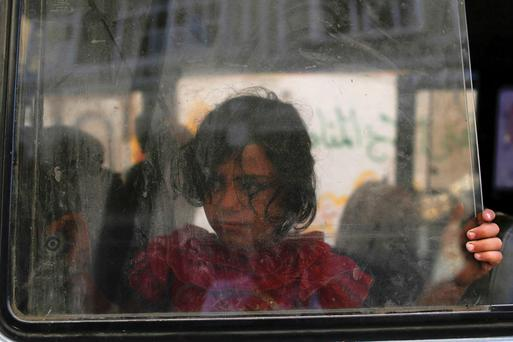 A girl looks through the window of a minibus as her family prepares to leave the Beit Hanoun neighbourhood in Gaza City