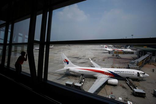 A boy looks at a Malaysia Airlines Boeing aircraft on the tarmac at Kuala Lumpur International Airport