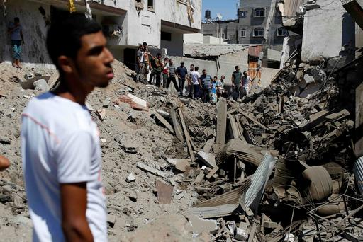 People look at a crater on the ground and damaged buildings, that witnesses said was caused by an Israeli air strike, in the Zeitoun neighbourhood in Gaza City