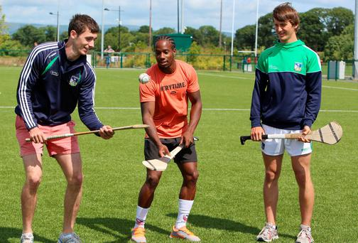 Carlin Isles (centre), who is reputed to be the fastest rugby 7s player in the world, gets some hurling tips from Limerick minors Barry Nash and Tom Morrissey ahead of this weekend's tournament. LIAM BURKE/PRESS 22