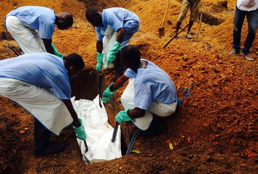 Volunteers lower a corpse, which is prepared with safe burial practices to ensure it does not pose a health risk to others and stop the chain of person-to-person transmission of Ebola, into a grave in Kailahun