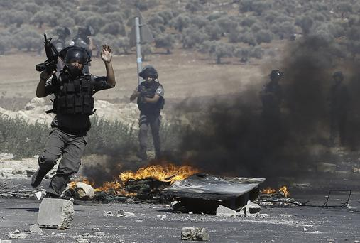 Israeli border guards clash with Palestinian protesters (unseen) following a demonstration in support of Gaza after Friday prayers at the Hawara checkpoint, east of the West Bank city of Nablus