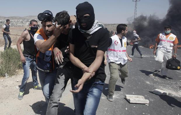 Palestinian paramedics look after injured protesters during clashes with Israeli security forces (unseen) following a demonstration in support of Gaza after Friday prayers at the Hawara checkpoint, east of the West Bank city of Nablus