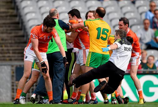Aaron Findon, Armagh, pushes Donegal team doctor Kevin Moran during an altercation in the first half