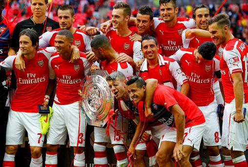 Arsenal players celebrate with the Community Shield after a 3-0 victory over Manchester City at Wembley