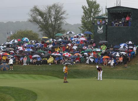 Chris Stroud putts in the rain on the 18th hole during the final round of the 2014 PGA Championship golf tournament at Valhalla Golf Club.