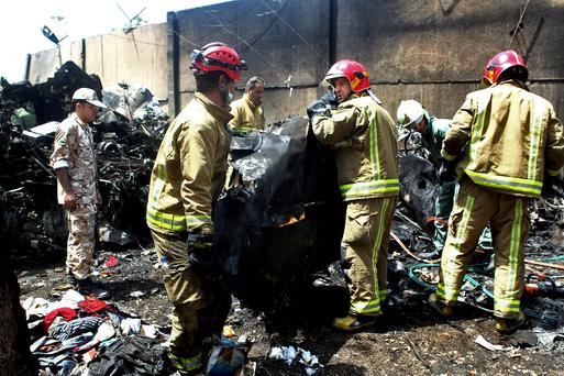 Iranian security and rescue personnel inspect the site of a passenger plane crash near the capital Tehran. AP