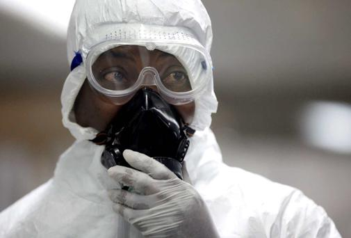 A Nigerian health official wearing a protective suit waits to screen passengers at the arrivals hall of Murtala Muhammed International Airport in Lagos, Nigeria. AP