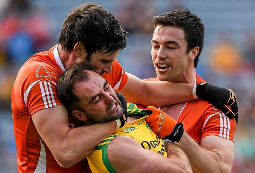 Donegal's Karl Lacey is grabbed by Aaron Findon and Aidan Forker of Armagh