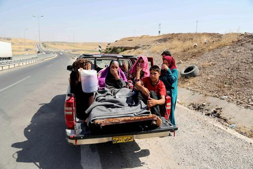 Displaced Iraqis ride on a truck on a mountain road near the Turkish-Iraq border, outside Dahuk, in Iraq. Islamic militants attacked the towns of Sinjar and Zunmar a few days ago. AP