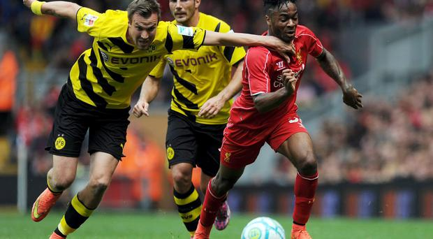 Raheem Sterling of Liverpool and Kevin Grosskreutz of Borussia Dortmund battle for the ball