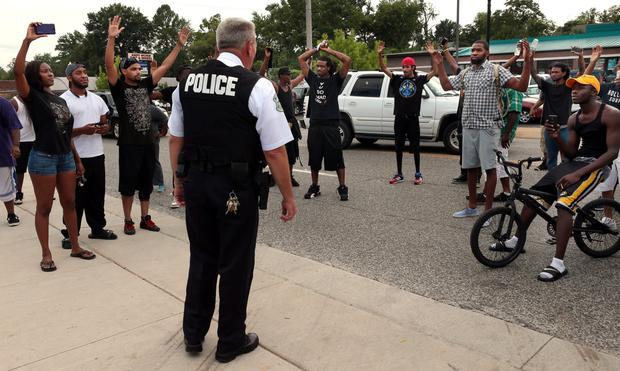 Protestors blocking Florissant Road raise their hands after being approached by police officers who asked them to stop blocking the street in front of the Ferguson police department