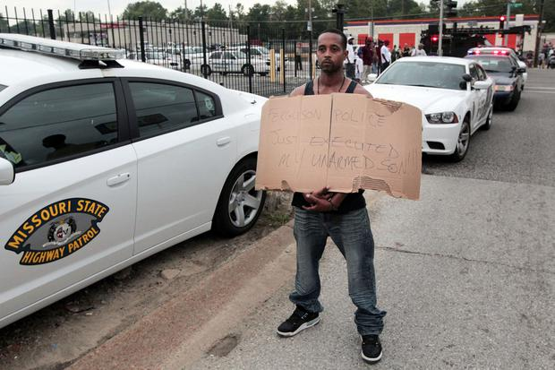 Louis Head, stepfather to 18-year-old Michael Brown who was fatally shot by police, holds a sign in Ferguson