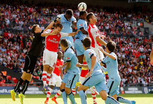 Arsenal's Wojciech Szczesny (L) finds his path blocked by team mate Nacho Monreal (2nd L) and Manchester City's Micah Richards (3rd L) during their English Community Shield soccer match at Wembley Stadium in London, August 10, 2014. REUTERS/Suzanne Plunkett (BRITAIN - Tags: SPORT SOCCER TPX IMAGES OF THE DAY)