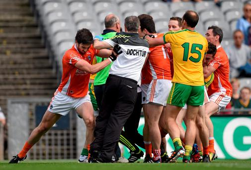 Aaron Findon, Armagh, pushes Donegal team doctor Kevin Moran during an altercation