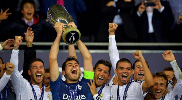 Real Madrid's captain Iker Casillas holds up the trophy beside his team mates after winning the UEFA Super Cup final against Sevilla at Cardiff City stadium