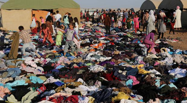 Displaced Iraqis from the Yazidi community look for clothes to wear among items provided by a charity organization at the Nowruz camp, in Derike, Syria. (AP Photo/ Khalid Mohammed)