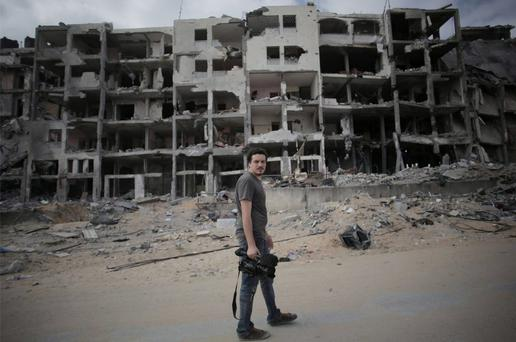 Video journalist Simone Camilli walks against a backdrop of destroyed buildings in Beit Lahiya in the Gaza Strip