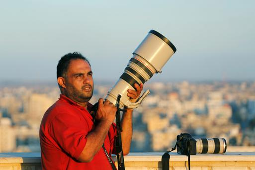 Hatem Moussa holds his camera, in Gaza City, Gaza Strip