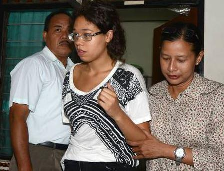 A police officer escorts suspect Lois Heather (19) during an investigation at a police office in Nusa Dua on Indonesian resort island of Bali