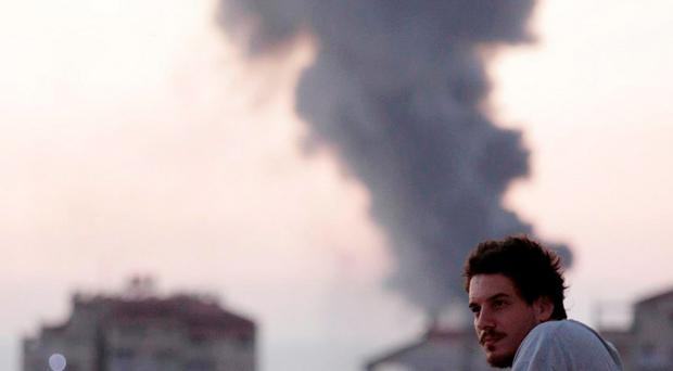 Associated Press video journalist Simone Camilli stands on a balcony with smoke from Israeli strikes billowing in the background, in Gaza City in this August 2014 photo. Italian journalist Camilli, three Palestinian bomb disposal experts and two other people were killed in Gaza on August 13, 2014 when unexploded munitions blew up, medical officials and police said. REUTERS/Lefteris Pitarakis/AP Photo/Handout via Reuters