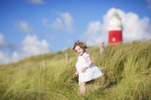 Cute toddler girl next to red lightshouse on beach