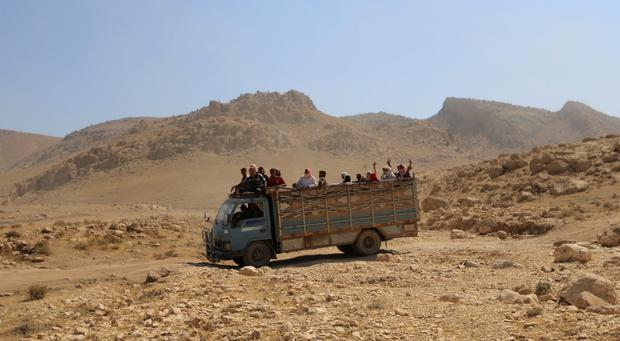 Displaced people from the Yazidi religious minority, fleeing violence from forces loyal to the Islamic State in Sinjar town, ride on a truck as they are evacuated from Mount Sinjar in northern Iraq