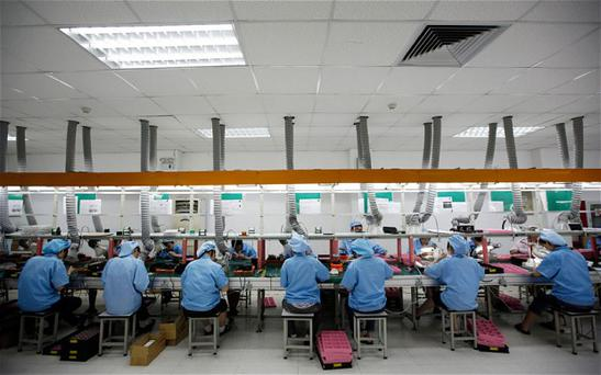 Employees work along a production line in a Chinese factory