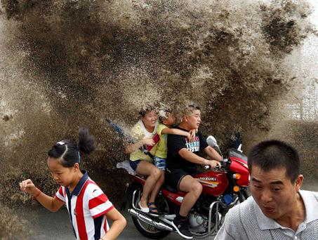 Visitors run away as waves caused by a tidal bore surge past a barrier on the banks of Qiantang River, in Hangzhou, Zhejiang province. Photo credit: REUTERS/Stringer
