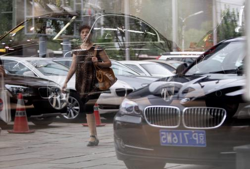 A woman is reflected on the glass wall of a BMW showroom as she walks past it in central Beijing